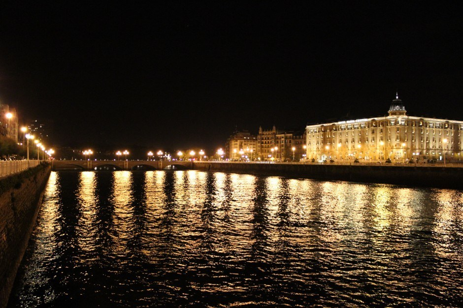 The lights of Hotel Maria Cristina shimmering on the river