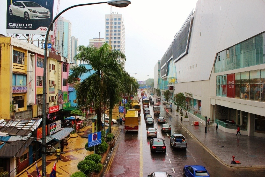 A walk in Johor Bahru, Malaysia: A street in Johor Bahru separating the old from new: The new mall on the right and old, slightly dilapidated store fronts on the left