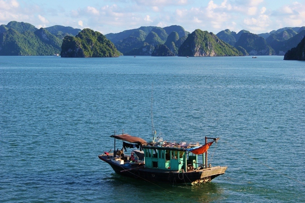 Halong Bay cruise: Fishing boats float amongst the Junk Boats on Halong Bay