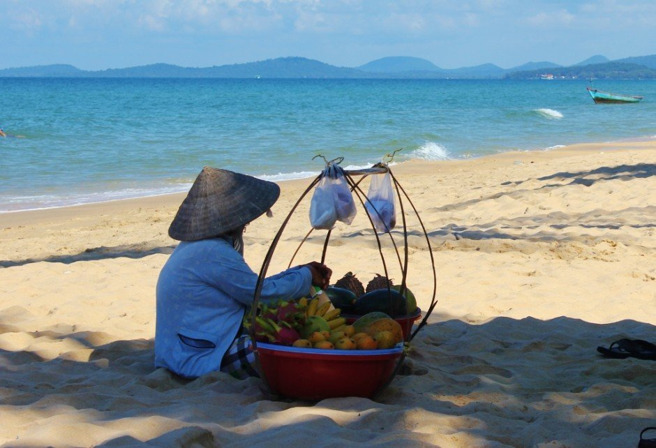 Phu Quoc Island, Vietnam: A woman selling fresh fruit on the beach rests in the shade