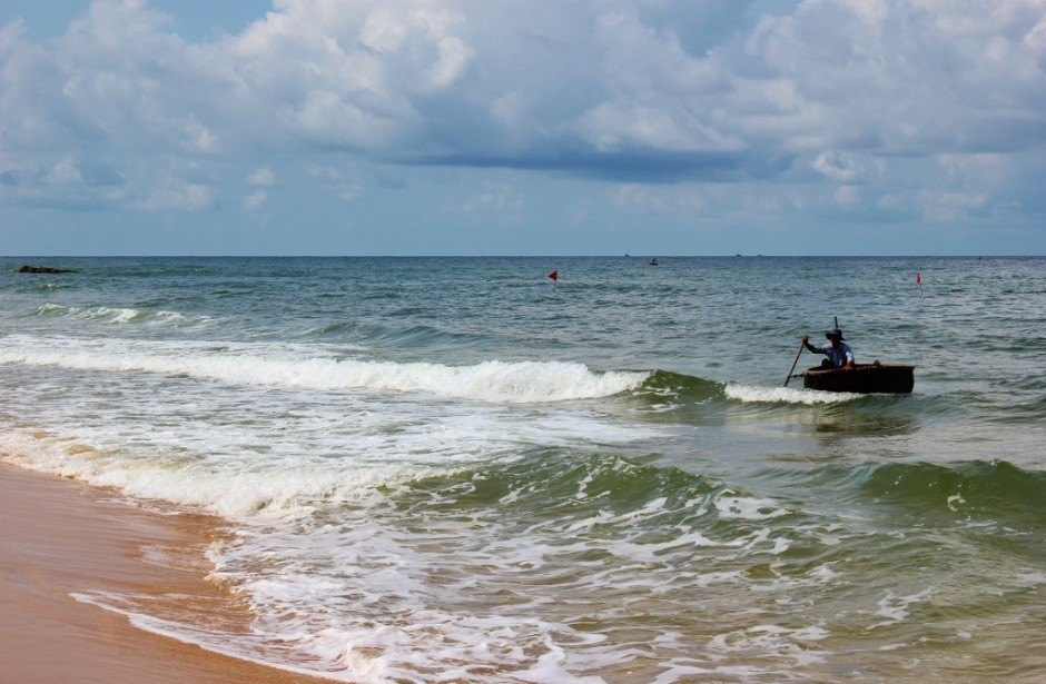 Phu Quoc Island, Vietnam: A fisherman rows to shore in a traditional round fishing boat