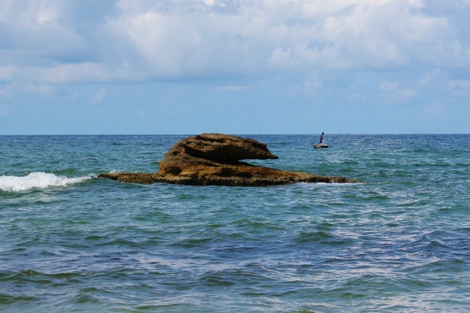 Phu Quoc Island, Vietnam: A rocky island protrudes from the water with a fisherman in the background
