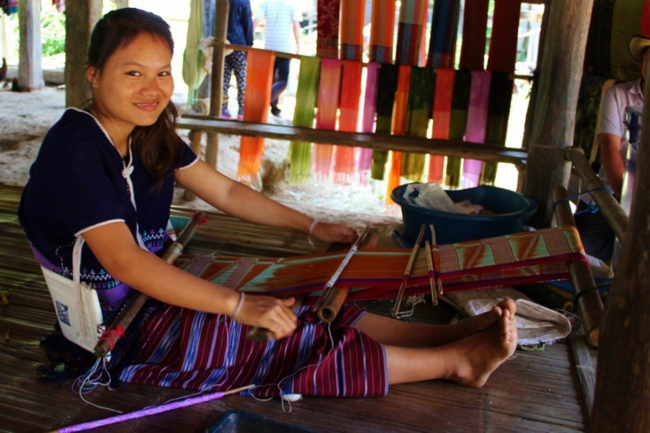 Chiang Mai trekking trip: Visiting a hill tribe village - a woman makes a scarf on a loom