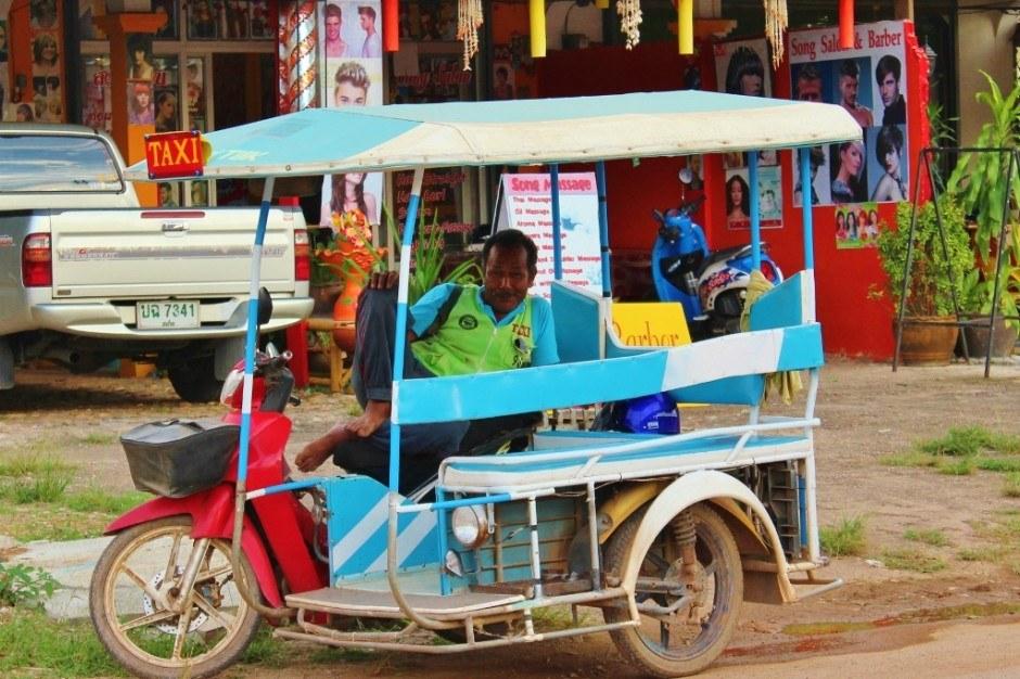 Daily life on Koh Lanta: Tuk-tuk driver waits for a fare