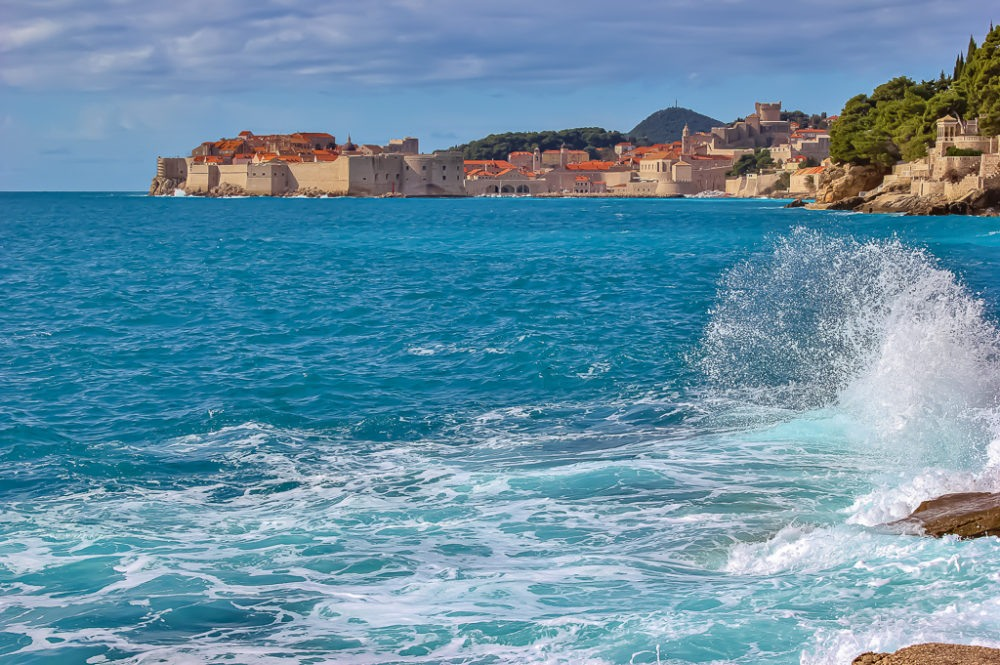 Wave crashing on rocks at secret viewpoint in Dubrovnik, Croatia