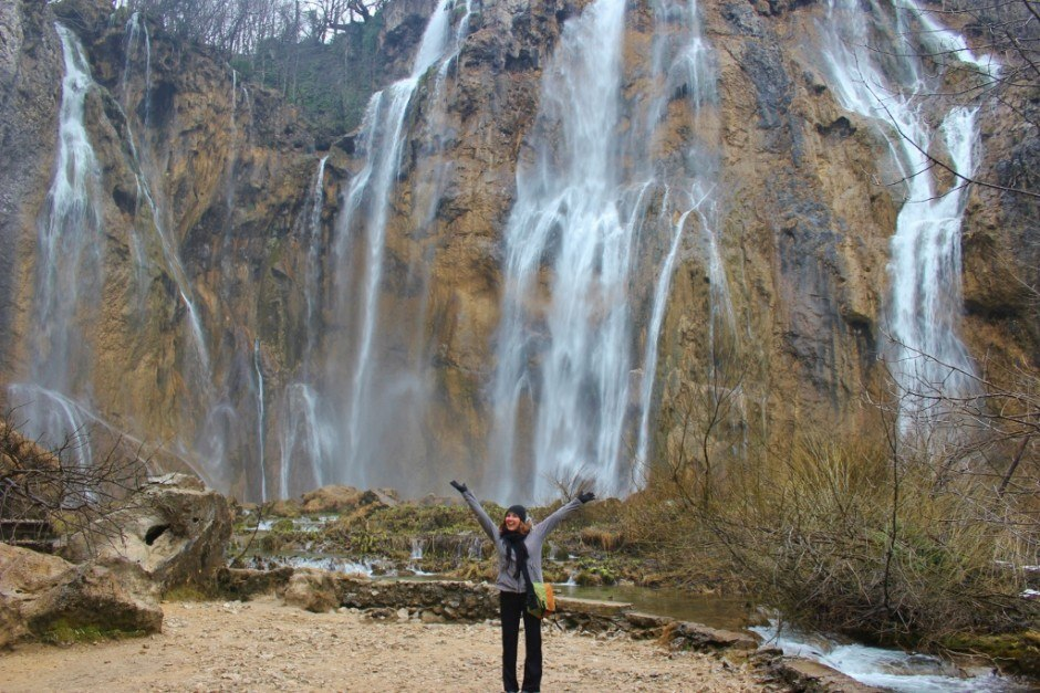 Visiting Plitvice Lakes: Sarah getting drenched in mist at the bottom of the Veliki Slap (Big Waterfall)