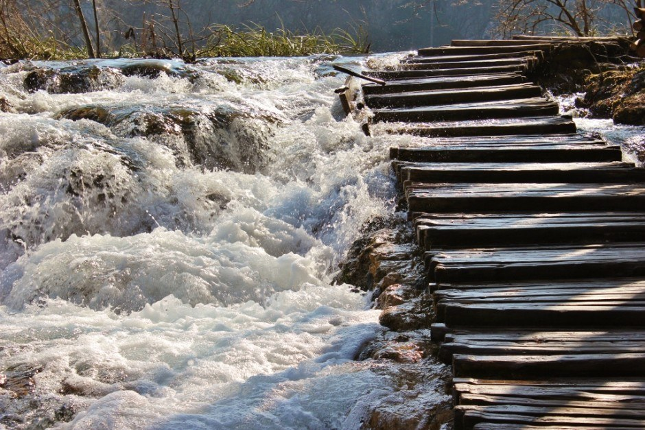 Visiting Plitvice Lakes: Water rushes below the planked pathways, sometimes seeping through.