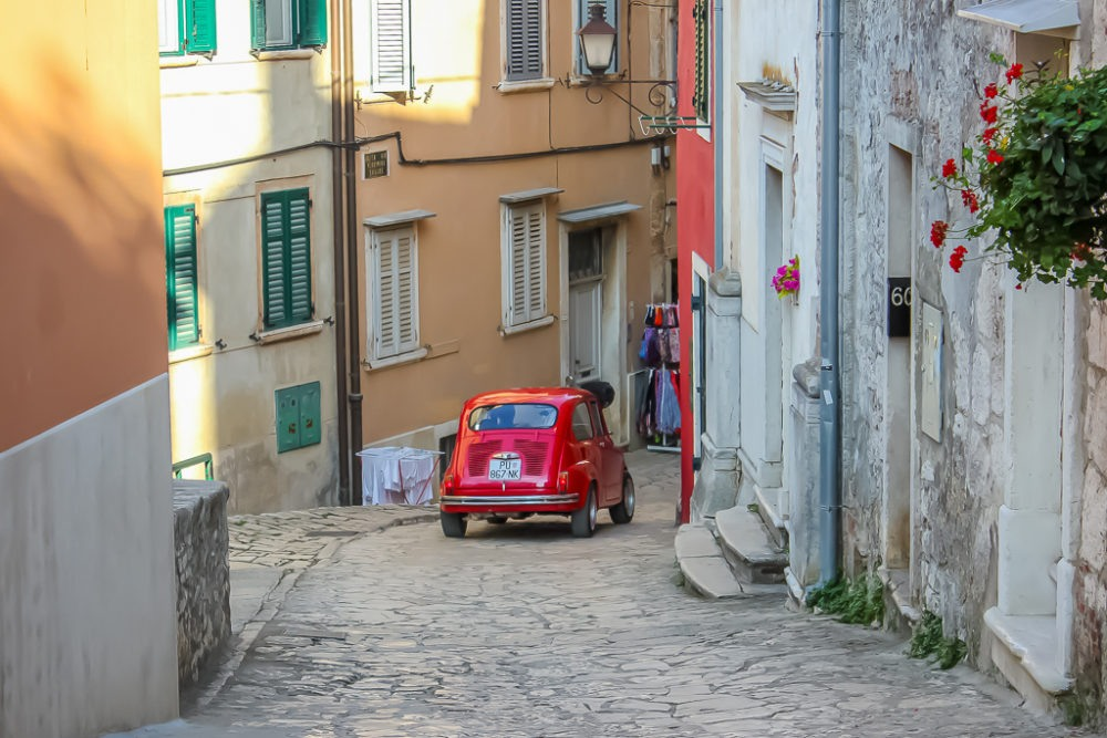 Small red car on narrow lane in Rovinj, Croatia