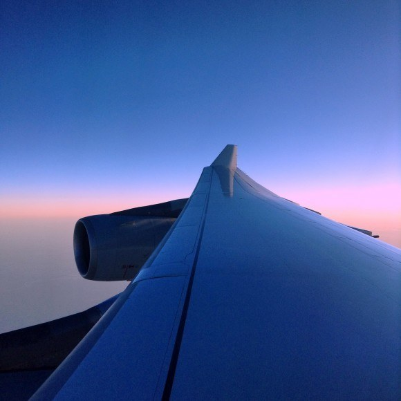 Window view of airplane wing taken while flying standby on connecting flights
