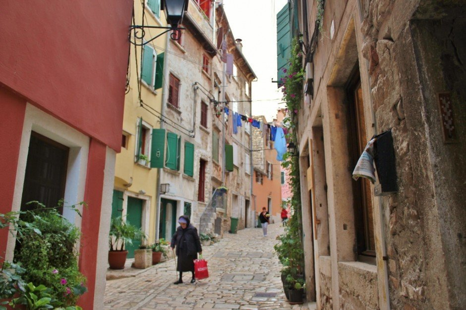 An old lady walks the cobblestone lanes in Rovinj, Croatia.