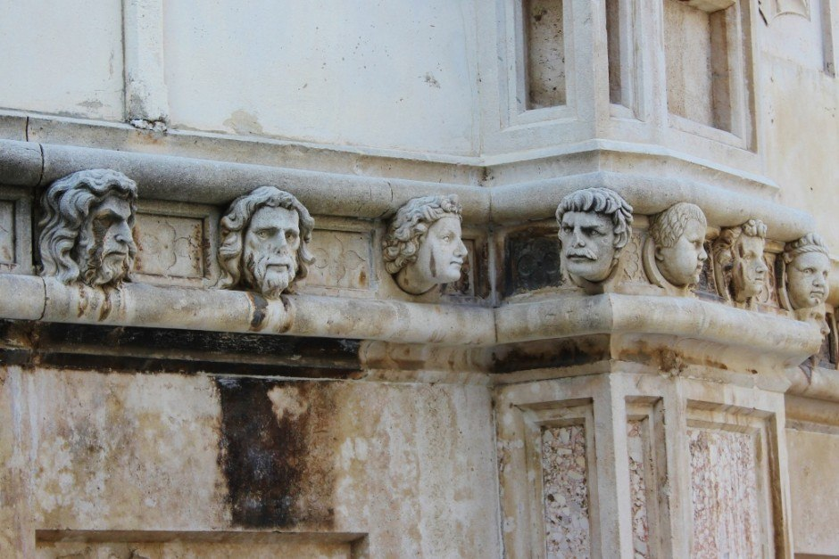 Larger than life, stone-carved heads protrude from the rear of St. James Cathedral in Sibenik, Croatia