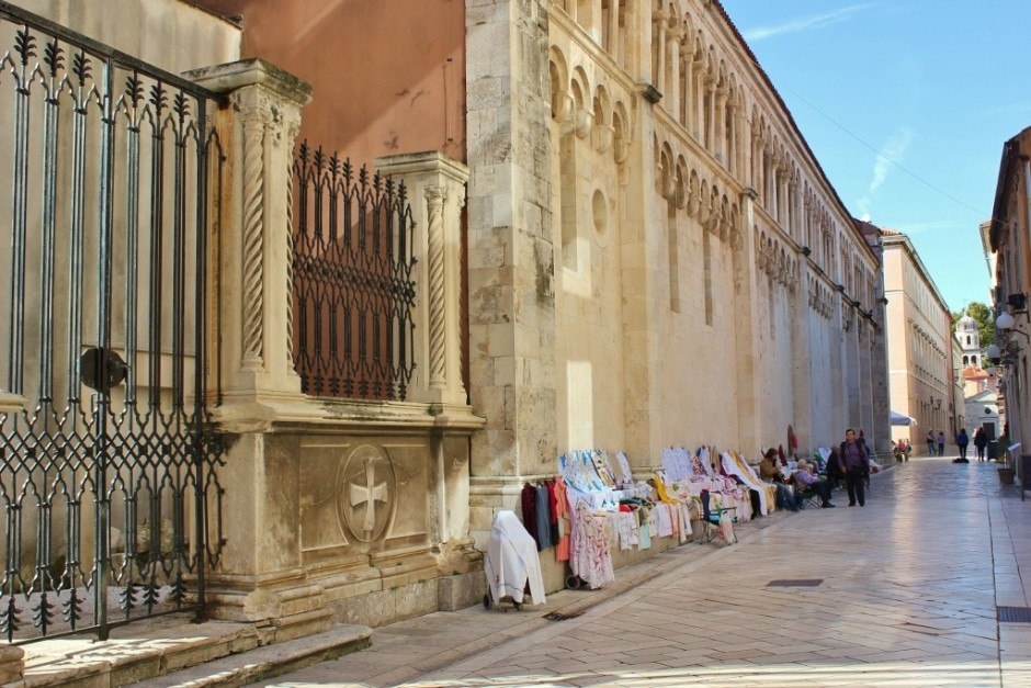 Local women knit and sell their products on the side of St. Anastasia's Cathedral in Zadar, Croatia