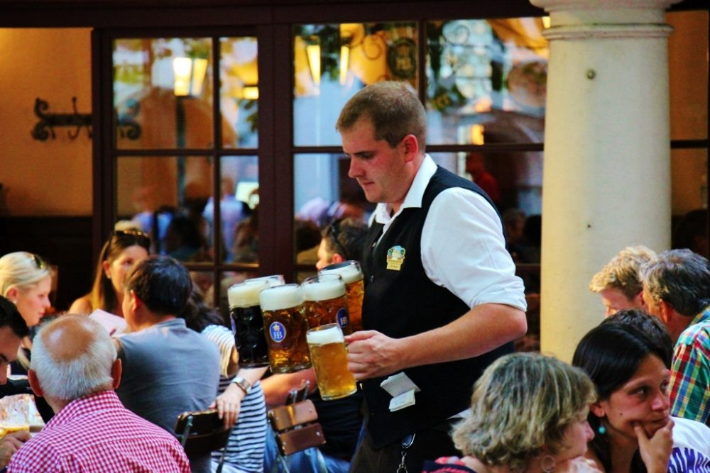 Sightseeing on a Layover in Munich Hofbrauhaus waiter carrying steins JetSettingFools.com
