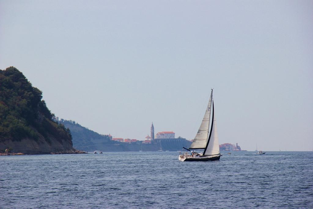 Sailboat passes Piran, Slovenia on water
