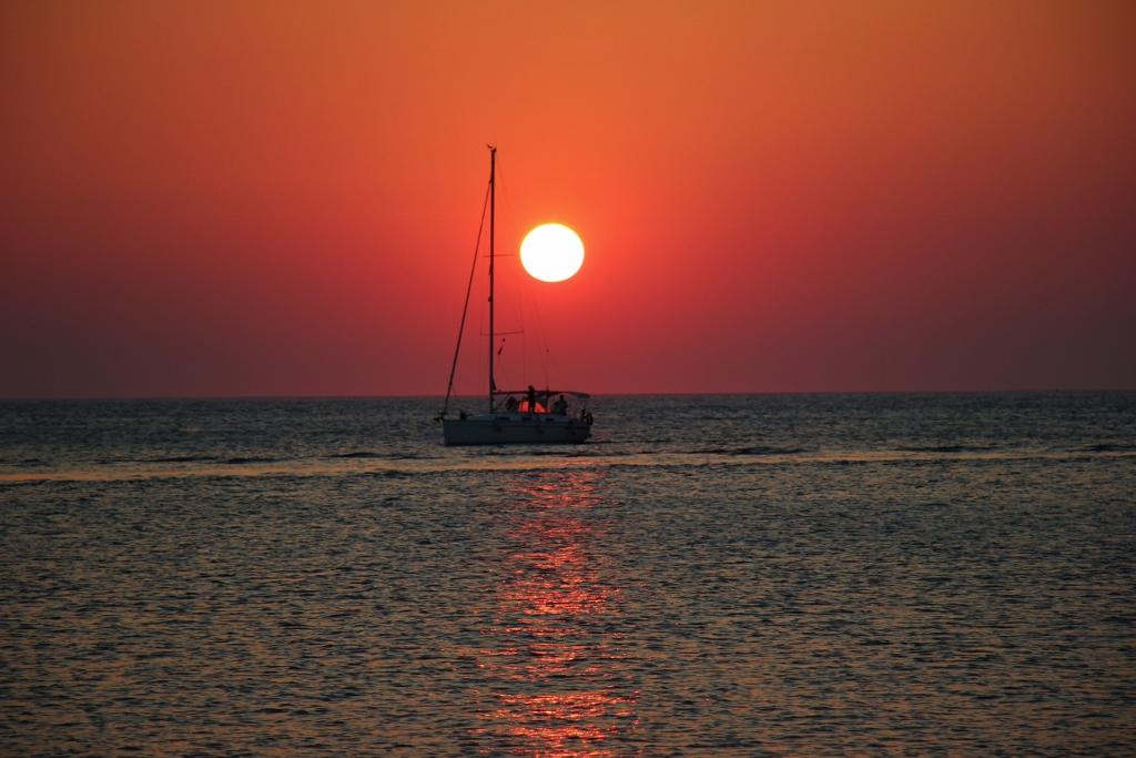 Orange ball sun at sunset with sailboat in Piran, Slovenia