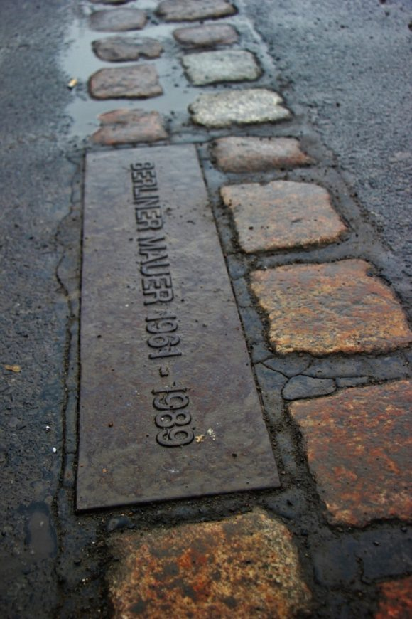 Bricks in the road mark the line of the Berlin Wall in Berlin, Germany