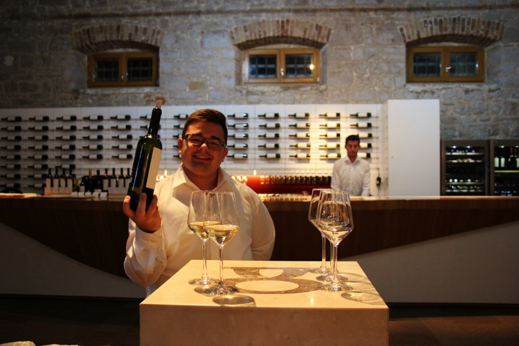 Waiter pours wine at Stina Winery in Bol, Brac, Croatia