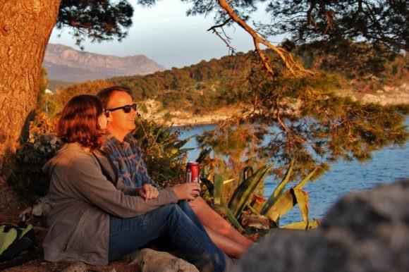 Couple watching sunset from St. Peter's Peninsula, Makarska, Croatia