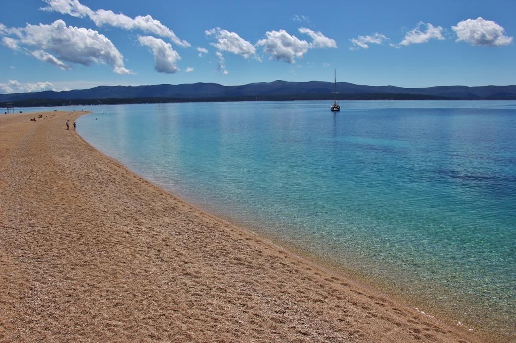 Zlatni Rat Beach and lone sailboat, Bol, Brac, Croatia