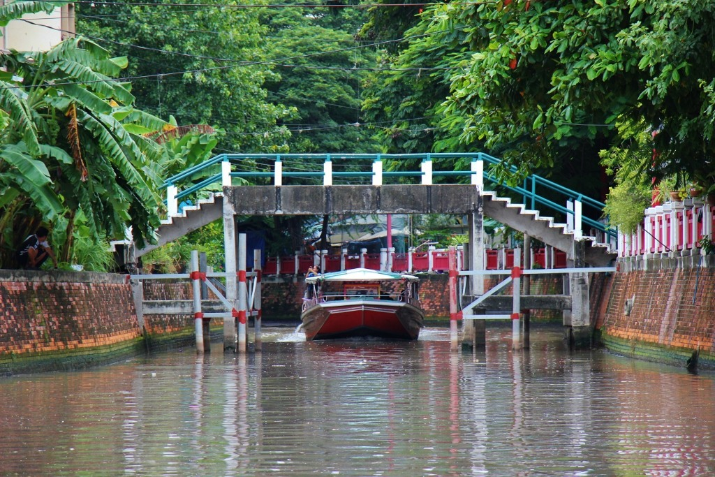Passenger boat sails under low bridge on Saen Saep Canal (Khlong) in Bangkok, Thailand