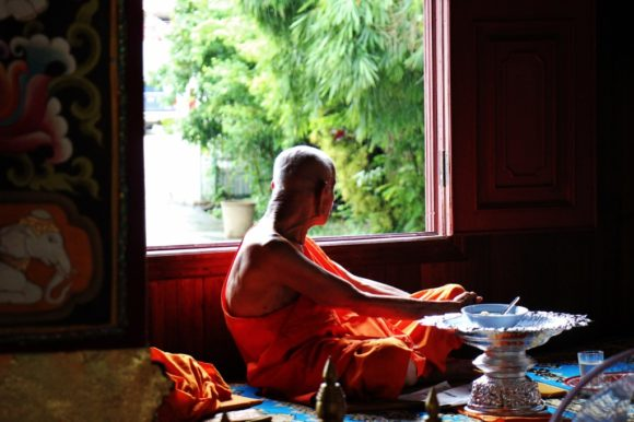 Monk looks out window in temple in Chiang Rai, Thailand