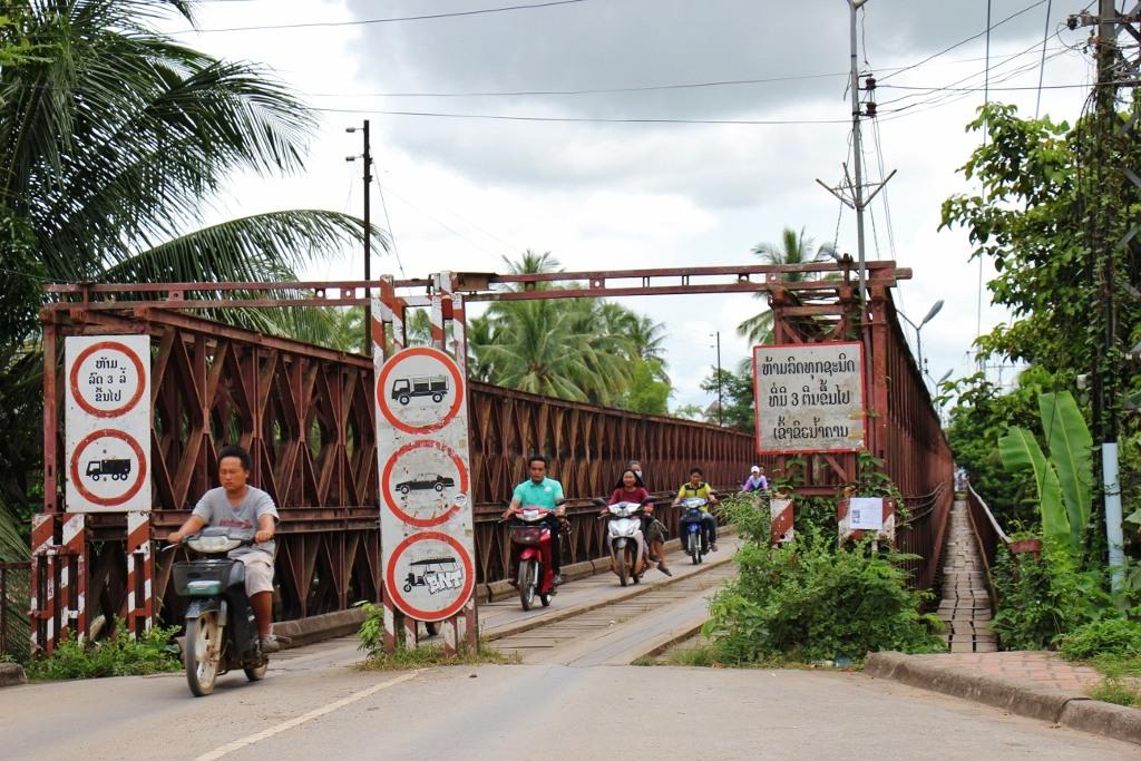 Scooters cros the Old Bridge in Luang Prabang, Laos