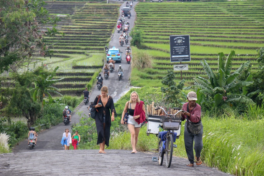 Man pushes bike up hill with line of traffic behind him in Canggu, Bali, Indonesia
